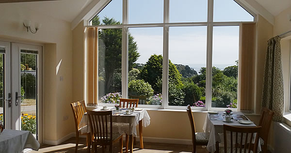 Relax over breakfast with views down a wooded valley to the sea